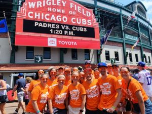 BibRave team wearing all orange in front of the Wrigley Field sign.
