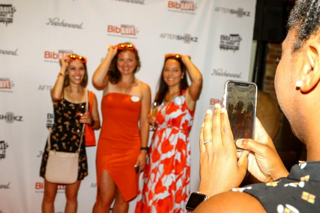 Steph taking a photo of 3 BibRave Pros on the Orange Carpet