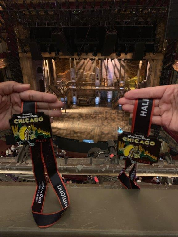 Holding our half marathon medals in front of the Hamilton musical stage.