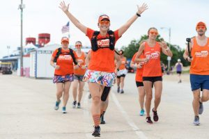 Running with the BibRave team in all orange with my arms outstretched in victory.