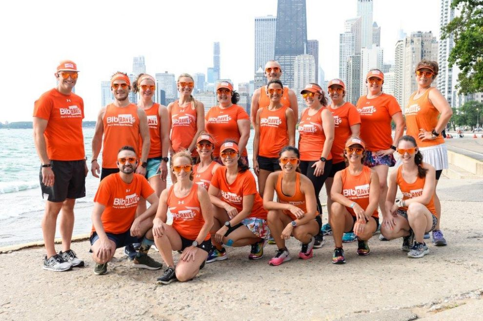 The BibRave Pro Summit team standing in front of the Chicago skyline at the lakefront.