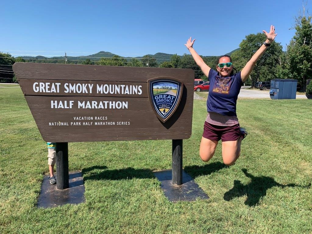 Jumping in front of the Great Smoky Mountain half marathon sign.