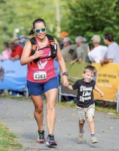 Running through the finish line with my youngest son who is wearing a Strong Like Mom shirt.