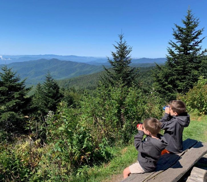 The boys sitting on a bench and testing their new binoculars looking over the mountainside.
