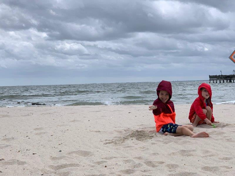 The boys playing in the sand at the beach. Wearing bright red coats and bundled up as it was pretty windy.