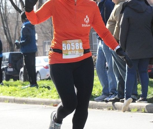 Wearing my BibRave orange shirt and beanie as I cross the finish line at the Hot Chocolate 15k.