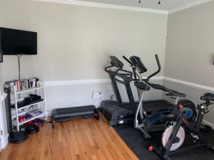 View of workout side of room with exercise equipment, wall-mounted tv, dvds and weights on shelving.