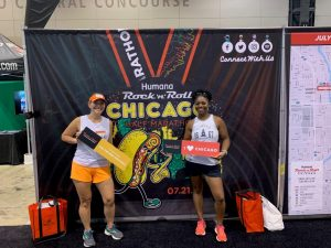 Standing in front of a Rock N Roll Chicago medal banner at the race expo.