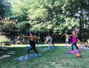 Teaching a group of students spaced out in my backyard doing the pose, Warrior 2.